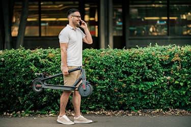 homme avec une trottinette électrique à la main